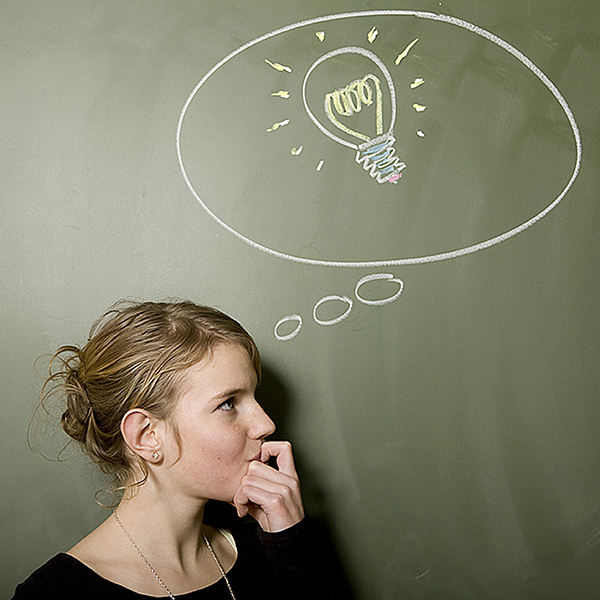 Girl stood next to chalk board with lightbulb in thought bubble drawn on